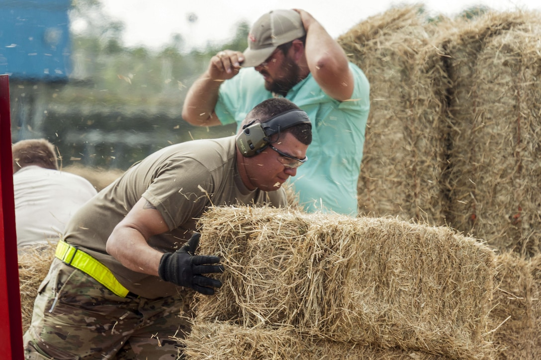 A service member lifts a bale of hay as small pieces of hay fly around him.