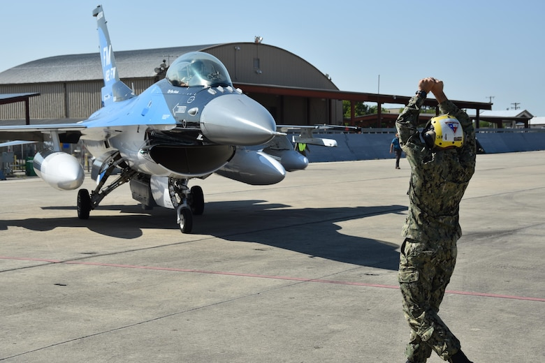 A sailor marshals an F-16 Fighting Falcon from Homestead Air Reserve Base, Fla., Sept. 6, 2017, at Naval Air Station Fort Worth Joint Reserve Base, Texas. The base serves as a safe haven for 14 military aircraft that relocated here due to Hurricane Irma's anticipated landfall in south Florida. (U.S. Air Force photo by Tech. Sgt. Charles Taylor)