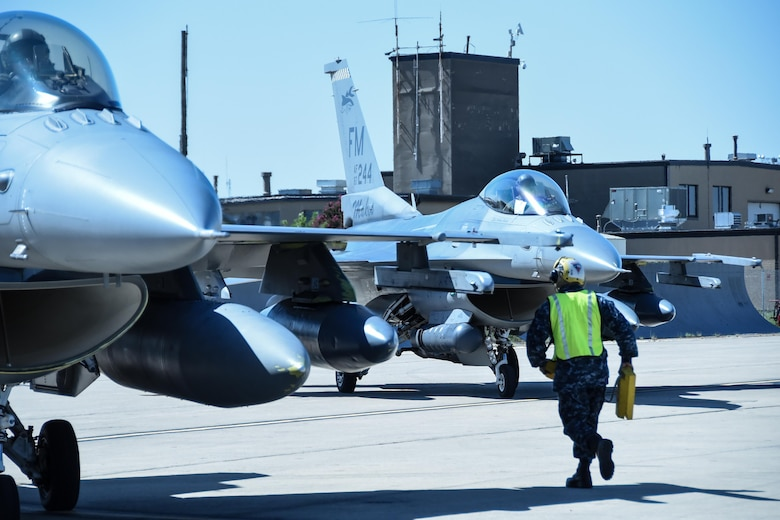 A Sailor runs to secure an F-16 Fighting Falcon from Homestead Air Reserve Base, Florida, Sept. 6, 2017, at Naval Air Station Fort Worth Joint Reserve Base, Texas. Fourteen aircraft relocated here today due to Hurricane Irma's anticipated landfall. The base serves as a safe haven for military aircraft that are in the path of the hurricane. (U.S. Air Force photo by Maj. Candice Allen)
