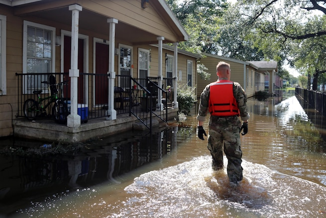A soldiers walks through floodwaters near homes.