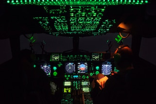 An Air Force C-17 Globemaster III cockpit lit up at night.