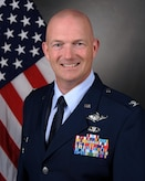 Official photo of bald white male colonel in Air Force blues standing in front of the US flag, which is red and white stripes, and blue square with white stars.