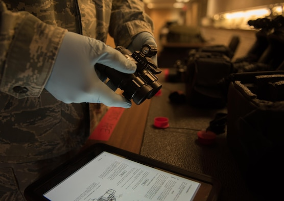 U.S. Air Force Staff Sgt. Robert Strayer, 1st Operational Support Squadron aircrew flight equipment technician, reviews the technical orders while inspecting night vision goggles for the night shift F-22 Raptor pilots during Red Flag 17-4 at Nellis Air Force Base, Nev., Aug. 24, 2017. The night vision goggles are used by the pilots during nighttime missions to increase their combat readiness. (U.S. Air Force photo by Staff Sgt. Carlin Leslie)