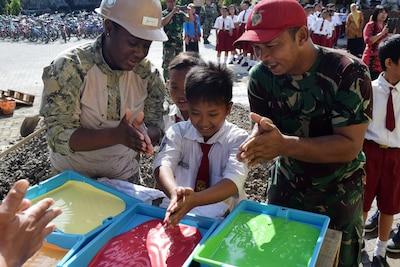 Navy Seaman Kiara Harris, assigned to Naval Mobile Construction Battalion 4, a local student and a member of an Indonesian marine battalion prepare to dip their hands in paint to leave their handprints on the schoolhouse that was built as part of the engineering civic action project during Cooperation Afloat Readiness and Training Indonesia 2016 in Surabaya, Indonesia, Aug. 30, 2016. The exercise's current iteration began Sept. 7, 2017. Navy photo by Petty Officer 3rd Class Santiago Guzman Jr.