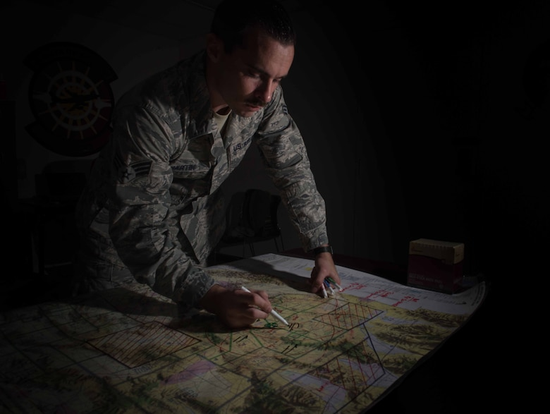 U.S. Air Force Senior Airmen John Hartin, 94th Fighter Squadron all source intelligence analyst, maps out ground-to-air target scenarios for Red Flag 17-4 mission planning at Nellis Air Force Base, Nev., Aug. 23, 2017. Utilizing intelligence from multiple sources, Hartin plots out each target point for the pilots' awareness allowing them to execute a mission. (U.S. Air Force photo by Staff Sgt. Carlin Leslie)