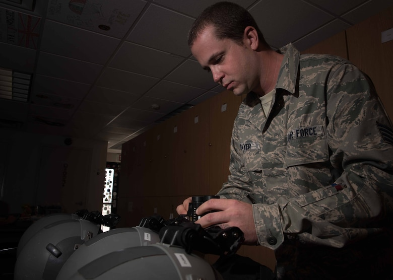 U.S. Air Force Staff Sgt. Robert Strayer, 1st Operational Support Squadron aircrew flight equipment technician, attaches night vision goggles to a pilot's helmet, during Red Flag 17-4 at Nellis Air Force Base, Nev., Aug. 24, 2017. While at RF, pilots fly daytime mission and night time missions to help keep current in all combat scenarios. (U.S. Air Force photo by Staff Sgt. Carlin Leslie)