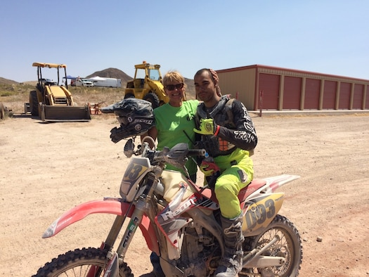 Airman and his mother pose for a photo with a dirtbike