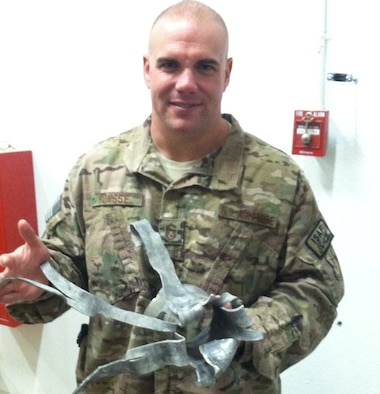 Senior Master Sgt. Jason Ronsse, Pacific Air Forces weather training standardization and evaluation and policy manager, holds up a rocket fragment he found at Forward Operating Base Shank during his deployment to Bagram Air Base, Afghanistan.