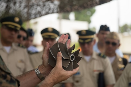 U.S. Marine Corps Col. Jaime Collazo, the commanding officer of Combat Logistics Regiment 15, 1st Marine Logistics Group, presents a scavenge fan blade to the students from the Columbian War College's General Staff Course at Camp Pendleton, Calif., Sept. 6, 2017. The Columbian War College established the General Staff Course as a requirement for promotion to the rank of lieutenant colonel for service members in the Colombian Army, Navy and Air Force. (U.S. Marine Corps photo by Lance Cpl. Roderick Jacquote)