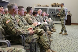 U.S. Army Soldiers sit in an auditorium while the commander briefs.