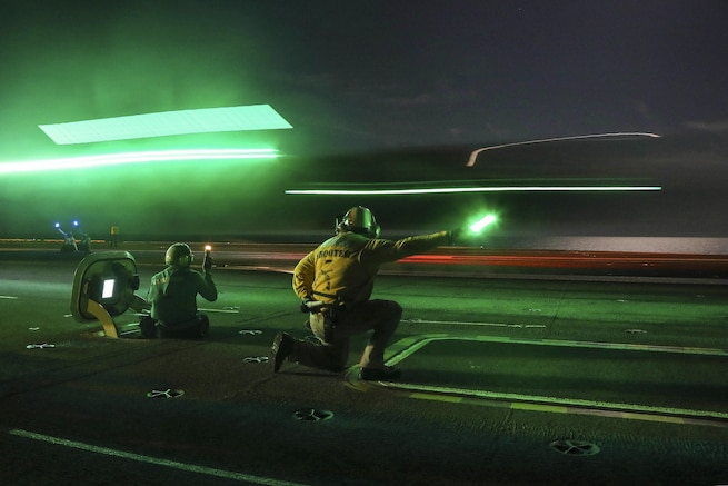 An aircraft lands on the flight deck of a ship at night as green lights flare.