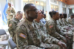 Soldiers sitting in an audience, listening to a presentation.