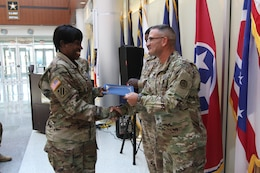 Soldier receives a handshake and graduation certificate from superior.