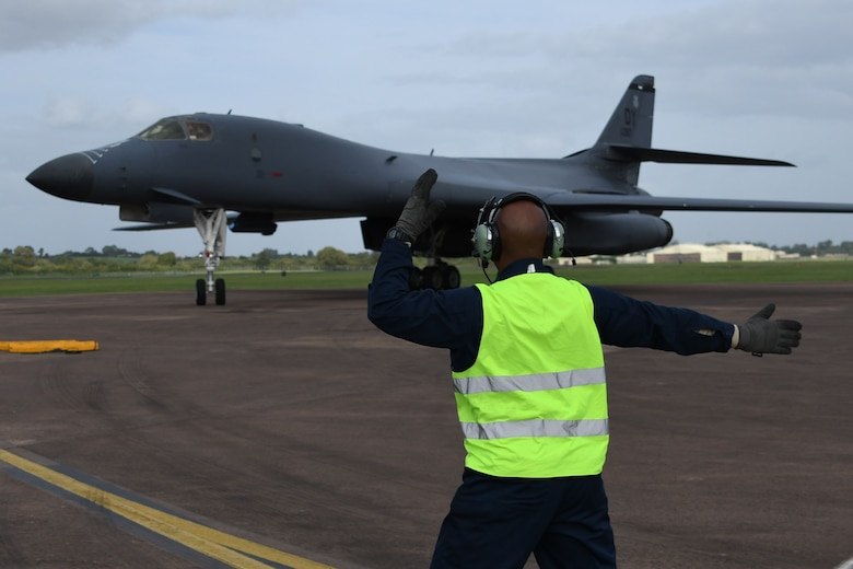 U.S. Air Force Tech. Sgt. Terance Thomas, 489th Bomb Group flight chief, marshals a B-1B Lancer after it landed at Royal Air Force Fairford, United Kingdom, Sept. 6, 2017.