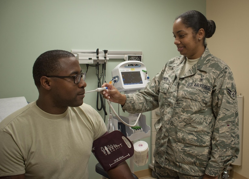 U.S. Air Force Airman 1st Class Alicia James, right, an aerospace medical service technician assigned to the 6th Medical Support Operations Squadron, takes a patient's temperature and blood pressure in the 6th Medical Group Clinic at MacDill Air Force Base, Fla., Sept. 7, 2017. The family health clinic sees approximately 180 patients daily and averages 39,000 appointments each year. (U.S. Air Force photo by Senior Airman Mariette Adams)