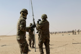 Three soldiers hoisting an antenna.