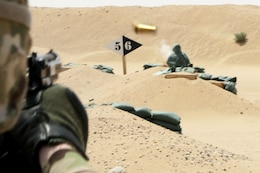 Over the shoulder shot of a soldier aiming at a target on a pistol range