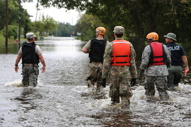 A group of soldiers and a police officer walk through knee deep water in a flooded street.