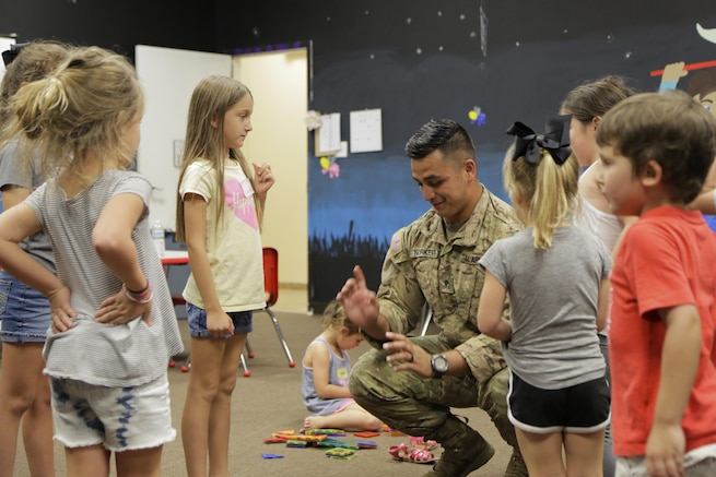 A soldier plays with a group of children.