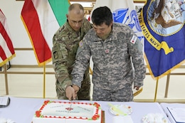 Two U.S. soldiers slice a cake.