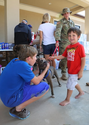 Two children play with a dog on a leash held by a soldier.