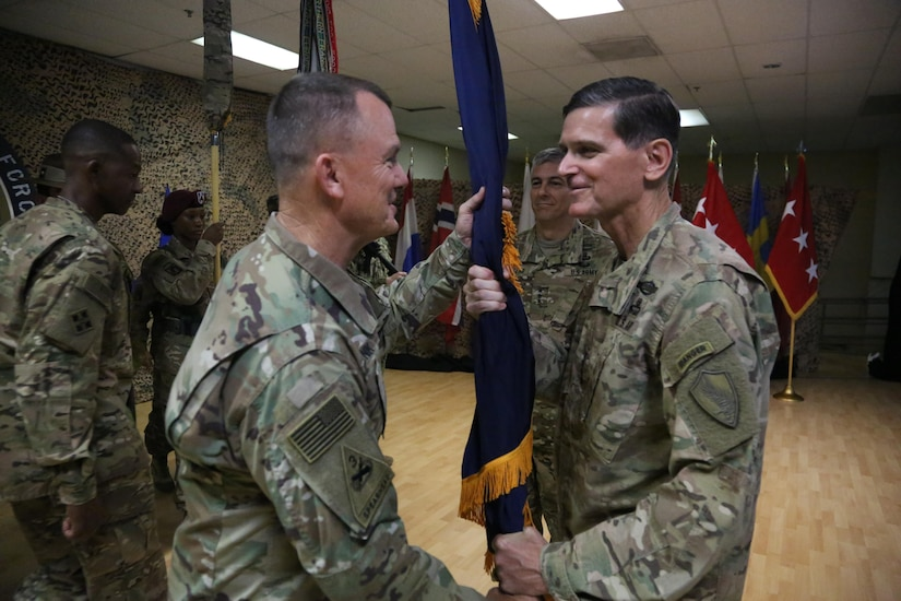 Army Lt. Gen. Paul Funk II, left, III Corps commander and the incoming commander of Combined Joint Task Force Operation Inherent Resolve, receives the CJTF-OIR colors from Gen. Joseph L. Votel, the commander of U.S. Central Command, during a transfer of authority ceremony in Southwest Asia, Sept. 5 2017. Funk assumed command from Lt. Gen. Stephen J. Townsend, commander of the XVIII Airborne Corps. Army photo by Staff Sgt. Ian Brown