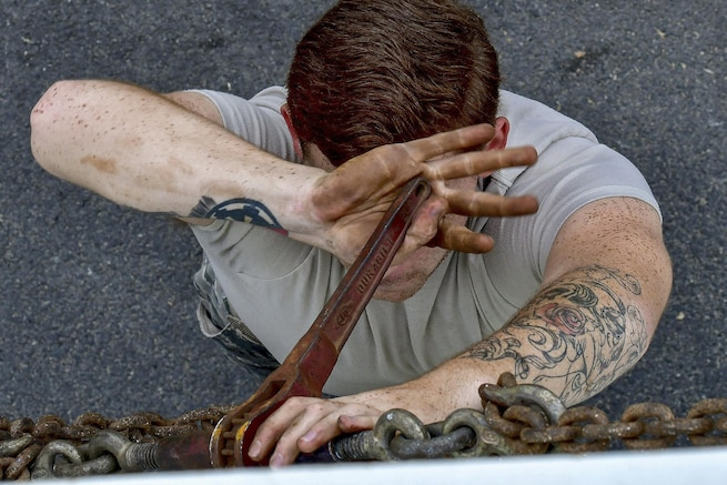 An airman tightens chains with a wrench that obscures his face.