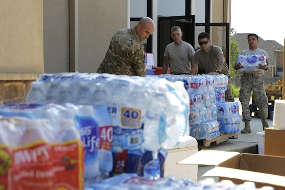 Soldiers pull pallets of water out a door.