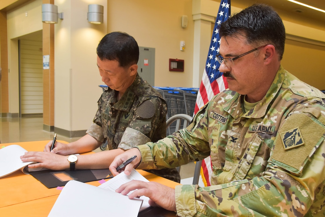 Col. Jeong Se-ok (left), Director General of Program Management, and Col. Garrett Cottrell, Deputy Military Chief United States Army Corps of Engineers Far East District, sign the United States Army Garrison Humphreys Armed Forces Exchange Acceptance Release Letter