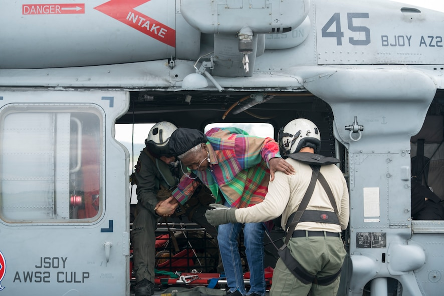 Naval Aircrewman (Helicopter) 2nd Class Jansen Schamp (Left) and Naval Aircrewman (Helicopter) 2nd Class Rion Johnson,  both assigned to the Dragon Whales of Helicopter Sea Combat Squadron (HSC) 28, assist with a medical evacuation during Hurricane Harvey relief efforts.  The Western Air Defense Sector provided critical communications relay between the Texas Emergency Operations Center and the U.S. Navy that rescued over 100 people from the school grounds.  (U.S. Navy Photo by Mass Communication Specialist 1st Class Christopher Lindahl)