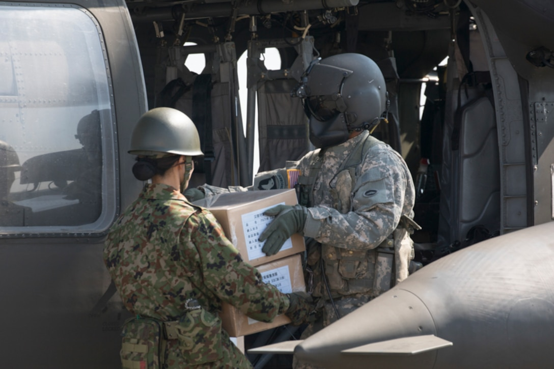 A U.S. Army UH-60 flight engineer passes simulated relief supplies to a Japan Ground Self-Defense Force member assigned to the 1st Logistics Regiment, JGSDF Nerima Station, at Yokota Air Base, Japan