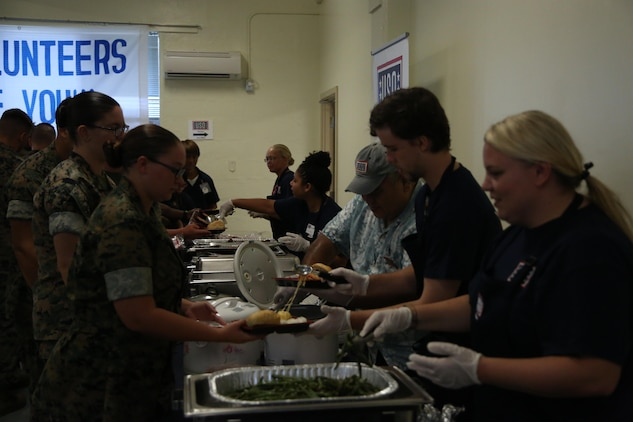 CAMP FOSTER, OKINAWA, Japan – Volunteers serve food to Marines after the grand reopening ceremony Aug. 30 at the Camp Foster USO, Okinawa, Japan.