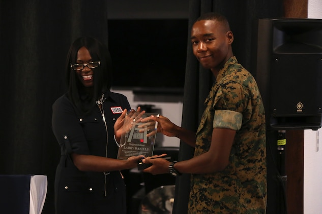 CAMP FOSTER, OKINAWA, Japan – Tamara Owens, left, presents Cpl. Larry Daniels the USO Okinawa Volunteer of the Quarter award Aug. 30 at the USO aboard Camp Foster, Okinawa, Japan.