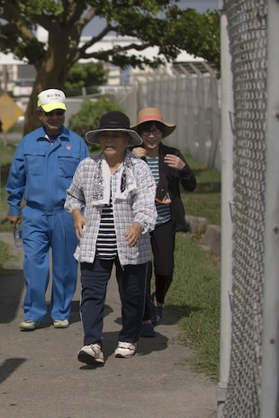 Members of the local community walk through the gate