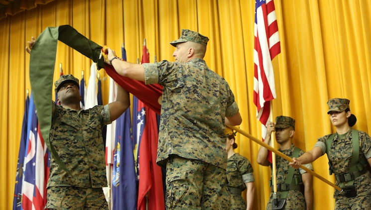 Col. Brian M. Howlett (left), commanding officer, III Marine Expeditionary Force Information Group, and Sgt. Maj. Mario P. Fields, sergeant major,  III MIG retire the III Marine Headquarters Group colors on Camp Courtney, Okinawa, Japan on Sept. 8, 2017.