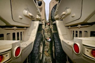 A soldier squeezes between two military vehicles to check the fuel.