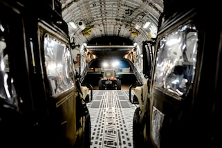 Airmen load vehicles and supplies onto a C-17 Globemaster III aircraft.