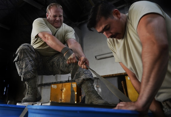 Tech. Sgt. Ryan Price, the 86th Logistics Readiness Squadron air delivery supervisor, pulls chords to tighten an airdrop bundle on Otopeni Air Base, Romania, Aug. 29, 2017. Aerial delivery Airmen, commonly known as riggers, are responsible for securing bundles and correctly rigging parachutes in order to ensure proper opening of the former. (U.S. Air Force photo by Airman 1st Class Joshua Magbanua)