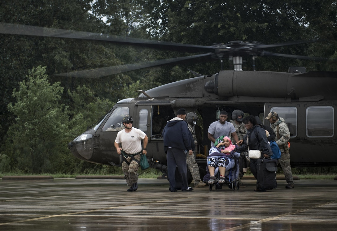 Airmen and Soldiers assist victims out of a UH-60 Black Hawk, Aug. 30, 2017, at the Orange County Convention and Expo Center in Orange, Texas. The 347th and 563rd Rescue Groups from Moody Air Force Base, Ga., Nellis AFB, Nev., and Davis-Monthan AFB, Ariz., sent rescue boat teams to Orange County, Texas, and the surrounding areas in support of the Federal Emergency Management Agency during Hurricane Harvey disaster response efforts. (U.S. Air Force photo by Staff Sgt. Ryan Callaghan)