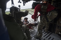 A 41st Rescue Squadron special missions aviator and a 38th Rescue Squadron pararescueman secure a basket carrying evacuees, Aug. 30, 2017, over a residence in the Houston, Texas area. The 347th Rescue Group from Moody Air Force Base, Ga. responded with its rescue aircraft and personnel in support of the Federal Emergency Management Agency after Hurricane Harvey brought flooding and destruction to parts of Texas. (U.S. Air Force photo by Tech. Sgt. Zachary Wolf)