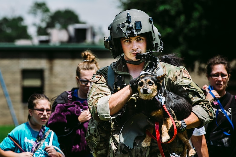 Senior Airman Austin Hellweg, a 129th Rescue Squadron special missions aviator, carries a dog and leads a family into an HH-60 Pavehawk for extraction to a safer location during the relief effort for Hurricane Harvey, Aug. 31, 2017, at Beaumont, Texas. The relief efforts have a conglomerate of active duty, Air National Guard and reserve units from all branches aiding the federal government to help Texas recover from Hurricane Harvey. (U.S. Air Force photo by Staff Sgt. Jordan Castelan)