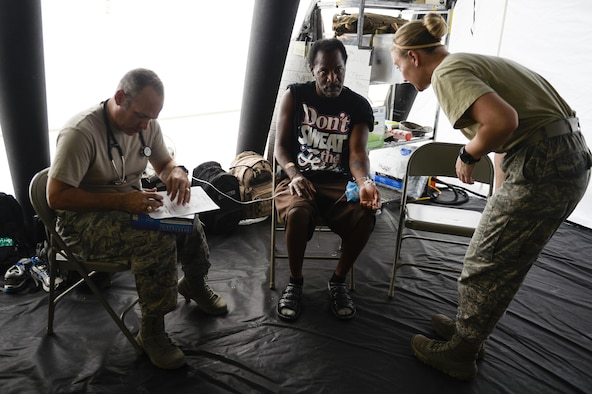 A patient receives care at a field hospital from Capt. Jerrod Taber, a physician's assistant, and Senior Airman Micah Battistoni, a medical technician, with the 149th Medical Group, Joint Base San Antonio, Texas Air National Guard, Sept. 3, 2017. The field hospital set up in the parking lot of the Baptist Hospitals of Southeast Texas as the hospital was only taking medical emergencies because of damage caused by Hurricane Harvey. (U.S. Air Force photo by Master Sgt. Joshua L. DeMotts)