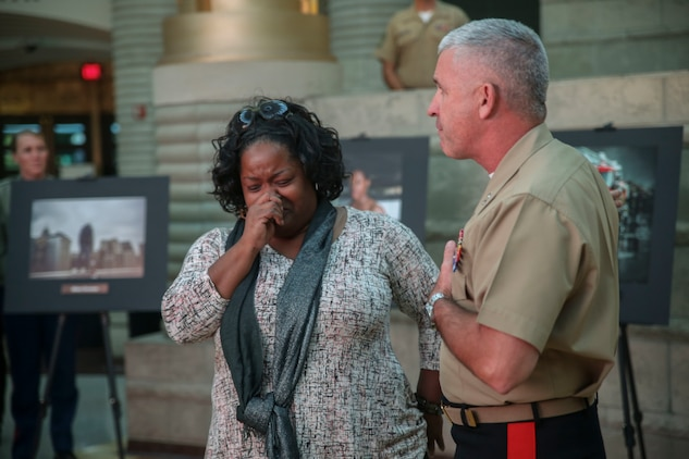 Maj. Gen. Paul Kennedy, commanding general of Marine Corps Recruiting Command, congratulates Felicia Tolbert, winner of the Battles Won photo competition in front of U.S. Marines with Marine Corps Recruiting Command and other competitors at the Charles H. Wright Museum of African American History during the Marine Corps' City Partnership visit in Detroit Sep. 7, 2017. The photo contest sought interpretations of Detroit's fighting spirit, and Tolbert's image depicted a woman who survived an abusive relationship. MCRC City Partnerships seek to align the Marine Corps with cities that share the essence of Marines - an irreducible fighting spirit. Scheduled events included High School visits supported by the Silent Drill Platoon, a Community Leaders Reception, a photography competition showcasing Detroit's fighting spirit, youth basketball and wrestling clinics, three on three basketball tournament, a cooking competition featuring an Expeditionary Field Kitchen, and more. MCRC leveraged existing partnerships with USA Wrestling, Women's Basketball Coaches Association and local contacts in the city to create events in celebration of the emerging partnership. Other City Partnerships in development include Baltimore, New Orleans, Chicago, Dallas, and Oakland, California. (U.S. Marine Corps photo by Sgt. Nathan Wicks)