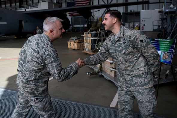 U.S. Air Force Maj. Gen. Timothy G. Fay, United States Air Forces in Europe and Air Forces Africa deputy commander, shakes hands with Airman 1st Class Peter Zuniga, 86th Logistics Readiness Squadron aerial delivery specialist, during an 86th Airlift Wing immersion tour in the dual bay on Ramstein Air Base, Germany, Sept. 7, 2017.