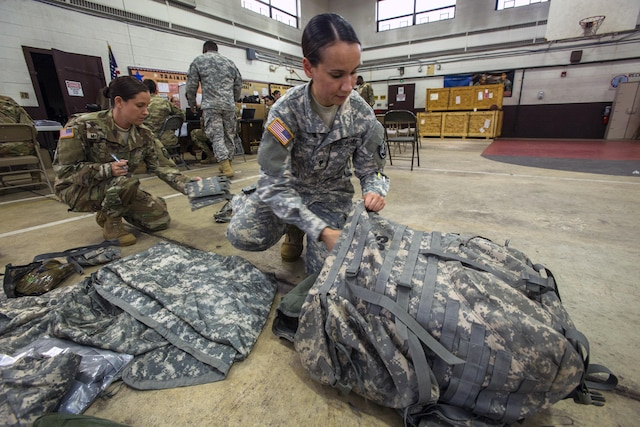 Troops kneel on a floor while packing gear.