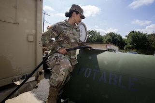 Army Pfc. Michaela Thomas fills a 400 gallon water trailer at Cape May Courthouse, N.J., as more than 130 New Jersey Army National Guardsmen prepare to deploy.