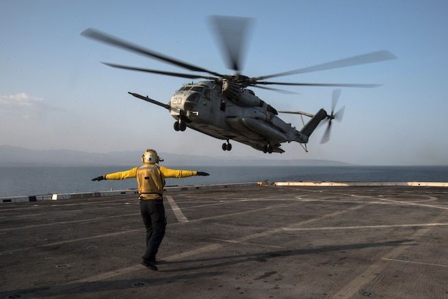 U.S. 5TH FLEET AREA OF OPERATIONS (Sept. 06, 2017) Aviation Support Equipment Technician 3rd Class Angus Moss, a native of Columbus, Indiana, assigned to the air department aboard the amphibious transport dock ship USS San Diego (LPD 22), directs an CH-53E Sea Stallion helicopter, assigned to Marine Medium Tiltrotor Squadron 161 (reinforced) on the ship's flight deck as part of Alligator Dagger exercise. Alligator Dagger is a dedicated, unilateral combat rehearsal led by Naval Amphibious Force, Task Force 51/5th Marine Expeditionary Brigade, in which combined Navy and Marine Corps units of the America Amphibious Ready Group and embarked 15th Marine Expeditionary Unit are to practice, rehearse and exercise integrated capabilities that are available to U.S. Central Command both afloat and ashore. (U.S. Navy photo by Mass Communication Specialist 3rd Class Justin A. Schoenberger/Released)