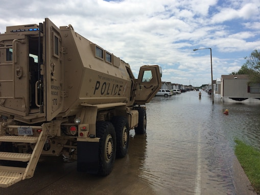 A mine resistant, ambush protected vehicle sits with doors open on a flooded street
