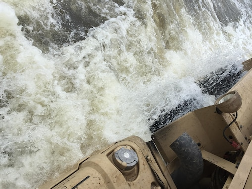 Floodwaters crash against a mine resistant, ambush protected vehicle as it drives
