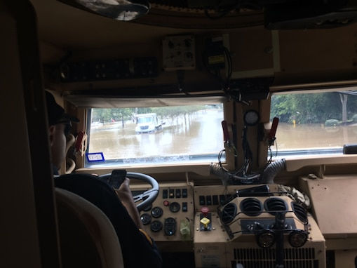 A driver sits behind the wheel of a mine resistant, armor protected vehicle as it goes through floodwater